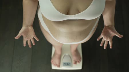 libra : Obese woman standing on scales desperately gesturing hands, fat belly, top view