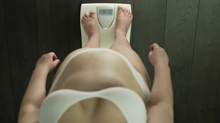 упитанность : Fat lady standing on bathroom scales with word obese on screen, health problems