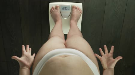 libra : Obese woman standing on bathroom scales, checking weight, anxious, top-view Vídeos