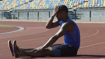 cansado : Latin athlete wiping sweat from forehead and rubbing tired from training legs Stock Footage
