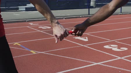 гонка : Closeup view of participant handing off baton to next runner, world championship Стоковые видеозаписи