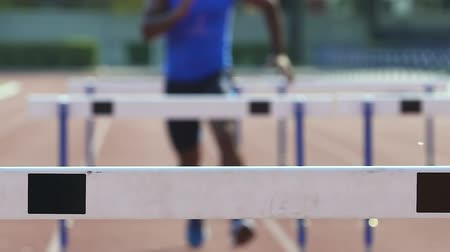 overcoming : Man running hurdle race, feeling strength and excellence in professional sport Stock Footage