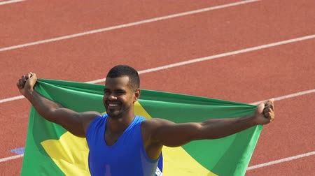 gururlu : Sportsman of Brazilian national team smiling at fan showing flag of his country Stok Video