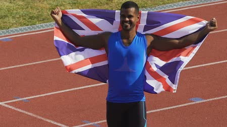 гордый : Happy athlete holding flag of his country in hands, Britain is proud of winner