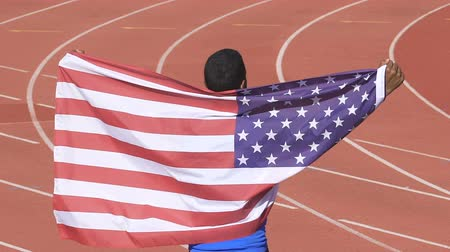 winnings : Sportsman holding flag of USA showing his victory in international competition Stock Footage