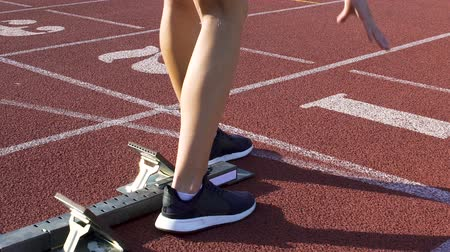 závodní dráha : Track runner woman preparing to run at starting blocks, active workout, slow-mo