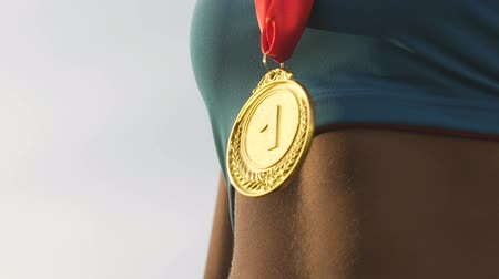 medal : Gold medal shining in the sun, hanging on athletes neck, victory and success Stock Footage
