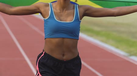 atleta : Mixed-race female athlete running on stadium with flag of Brazil, patriotism Stock Footage