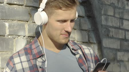 прослушивание : Handsome young man in headphones smiling, looking at smartphone screen, chatting