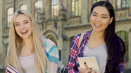 phd : Multiethnic females with notebooks smiling at camera, high school education