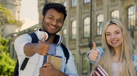 admission : Female and male students smiling at camera, showing thumbs-up, quality education Stock Footage
