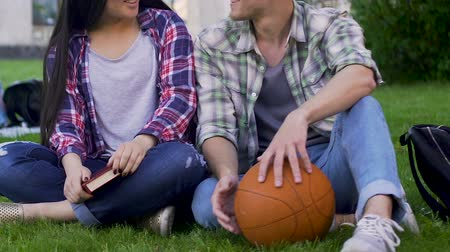 interessado : Male and female students sitting on lawn closely, having conversation, flirting