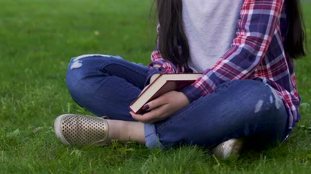 stories : Young woman sitting on grass, holding closed book, recreational activity, relax