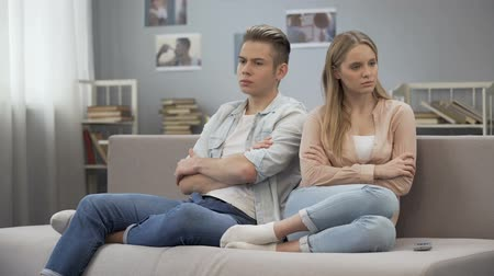misunderstanding : Two frustrated teenagers sitting on couch turn way, quarrel misunderstanding Stock Footage