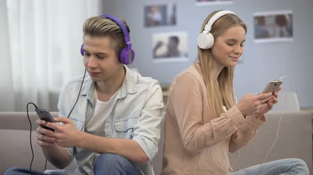 общий : Smiling young people listening to music together, getting to know each other