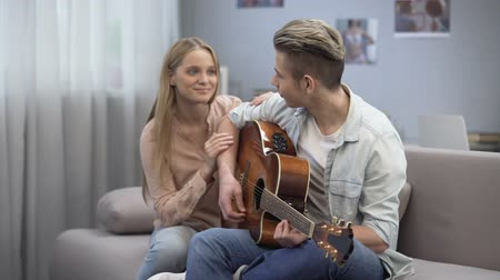 guitarrista : Teen student playing song and girlfriend hugging him, romantic love confession