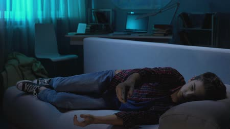 switching : Teenager relaxing on sofa and falling asleep in front of TV, free time at home Stock Footage