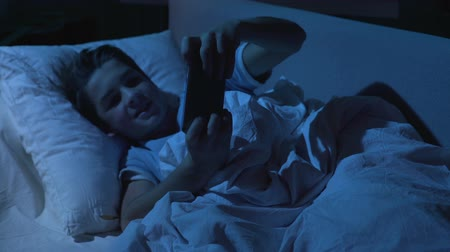 bezsennosć : Excited young boy enjoying game round on smartphone in bed during sleeping time