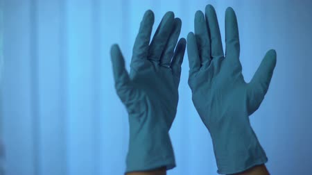 incapacidade : Person looking at hands in latex rubber gloves, taking them off with irritation