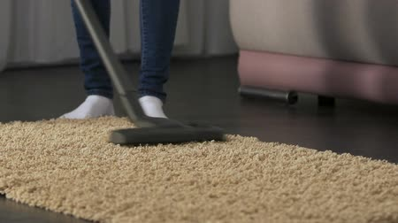 avoiding : Lady carefully vacuuming mat at home, avoiding dust accumulation and allergy Stock Footage
