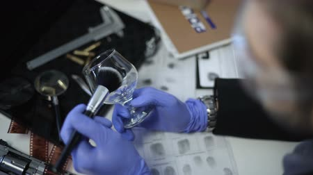 forensic : Detective in gloves lifting fingerprints on wine glass, using brush and powder