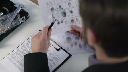 identifikace : Detective watching fingerprints on paper, using magnifying glass, solving murder