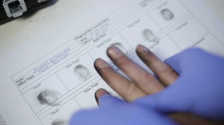 fingerprinting : Police officer in exam gloves taking fingerprints from suspect, hands closeup
