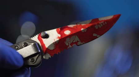 zdjęcia seryjne : Forensic examination of knife with blood, conclusive evidence, hand closeup