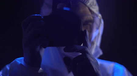 serial : Criminalist taking evidence pictures at crime scene, night time, close up Stock Footage