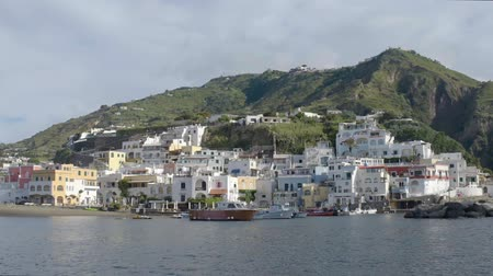 плотно : Island coast with white houses built densely up hill, view from across harbor