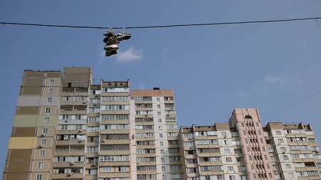 cadarço : Old shoes hanging high on power lines in dormitory city area, drug dealers sign Vídeos