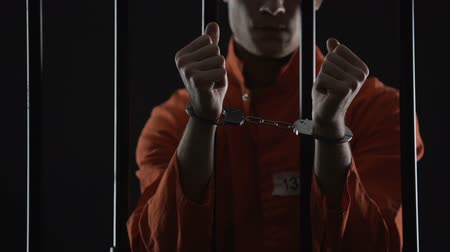 kajdanki : Prisoner in orange uniform showing handcuffs, looks angry and disappointed