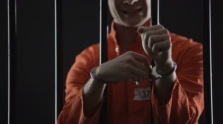 unlocking : Criminal trying to escape from prison, unlocking handcuffs with stolen key