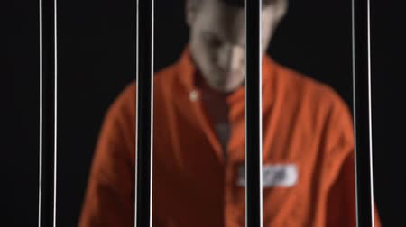 veredito : Arrested man in orange suit approaching to prison bars, death penalty judgment