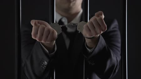 venality : Man in suit showing hands in handcuffs behind bars, bribery, financial fraud