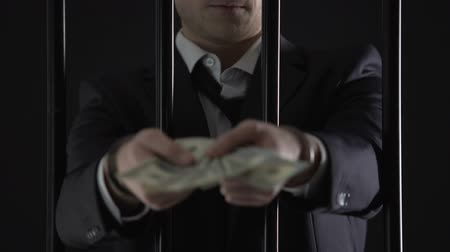 forgery : Handcuffed businessman holding dollar banknotes, tax evasion, money laundering