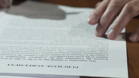 договориться : Male hands signing purchase deal documents on the table, apartment ownership