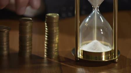 зарабатывать : Rich man putting coins on piles, view on sandglass measuring time, finance