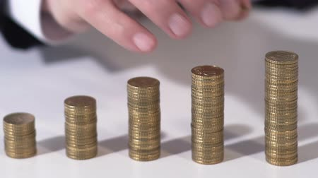 lucrative : Successful businessman putting coin on pile, investment in future, closeup Stock Footage