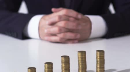 banqueiro : Business person sitting in front of coin piles, banking and income growing Stock Footage