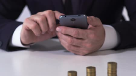 lucrative : Male banker working on smartphone with coin piles table, checking currency rate