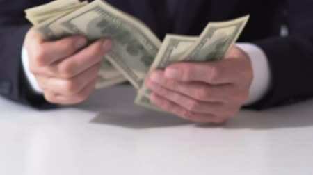 lucrative : Rich male counting dollar banknotes, hands of businessman estimating income Stock Footage