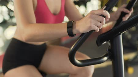 wristband : Healthy slim female wearing fitness bracelet riding exercise bike at sports club