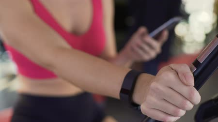 womans hand : Fitness bracelet on womans hand, athletic girl riding exercise bike, closeup Stock Footage