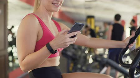wristband : Athlete with fitness bracelet riding exercise bike and chatting on cellphone