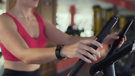 wristband : Sporty girl riding exercise bike and monitoring distance on fitness bracelet Stock Footage