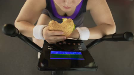 motivo : Corpulent female eating fatty burger while riding stationary bike, fast food