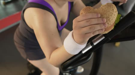 motivo : Overweight female eating fatty burger while riding stationary bike, lifestyle