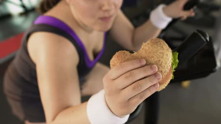 motivo : Fat woman riding stationary bike and eating tasty burger in gym, unhealthy diet