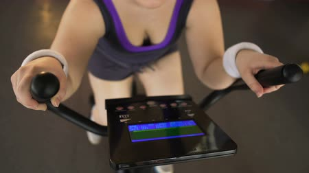 looking distance : Plump single-minded girl working hard on stationary bike at sports club, workout Stock Footage